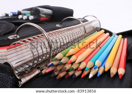 Colorful sharpened  pencil crayons for school  beside  three ring binder containing pens and pencils in pocket