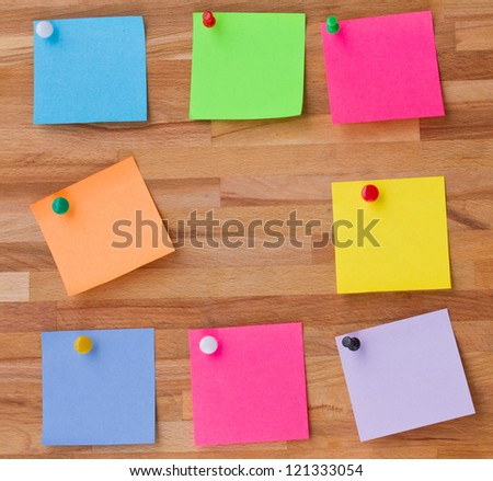 colorful sheets of paper on wooden board background - stock photo