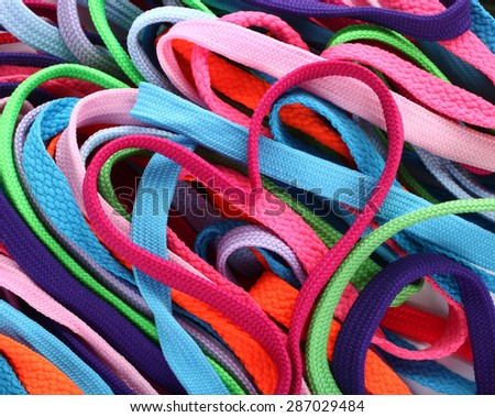 Colorful shoe laces and heart shaped pink shoelace - stock photo