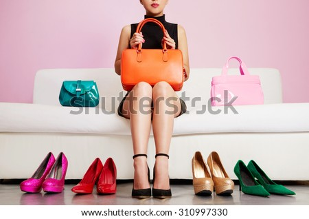 Colorful shoes and bags with woman sitting on the sofa. Shopping and fashion images. - stock photo