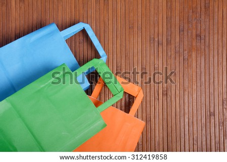 Colorful shopping bags over wooden background. Copyspace. - stock photo