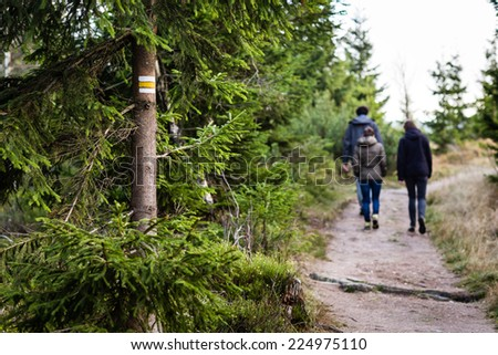 Colorful signs for hiking tourism in Czech Giant Mountains. Group of tourists walk on the patch through forest. - stock photo