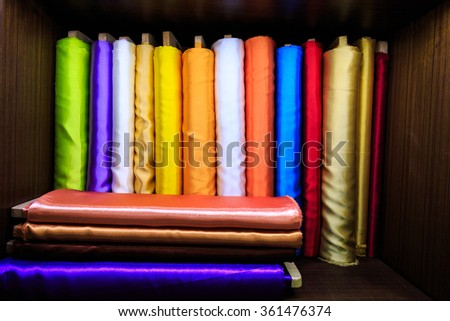 Colorful silk fabrics on roll on a shelf - stock photo
