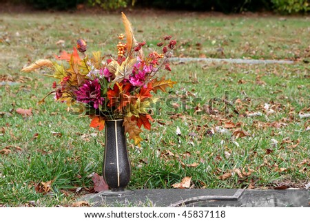 colorful silk flower vase in autumn cemetery - stock photo