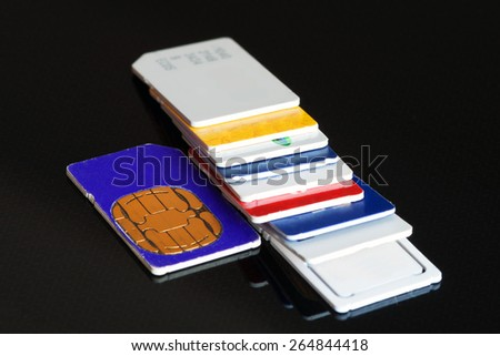 Colorful sim card on a black background, close up. - stock photo