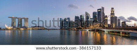Colorful Singapore business district skyline after sun set at Marina Bay. Panoramic image.