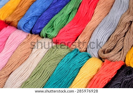 Colorful skeins of floss as background texture close up