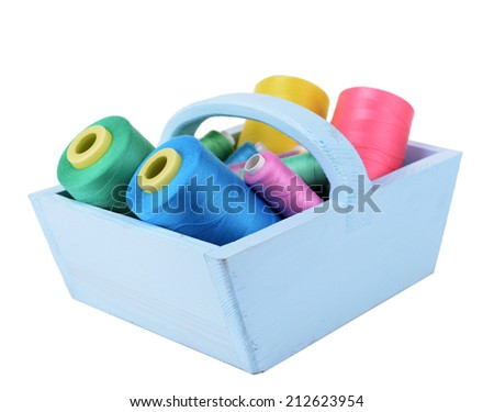 Colorful skeins of thread in wooden box isolated on white
