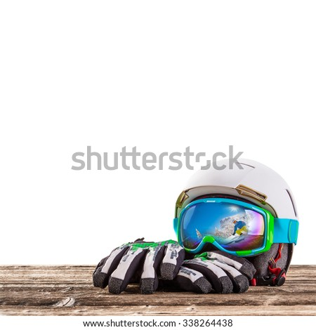 Colorful ski glasses, gloves and helmet on wooden table. Winter ski theme. - stock photo