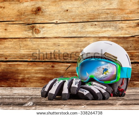 Colorful ski glasses, gloves and helmet on wooden table. Winter ski theme. - stock photo