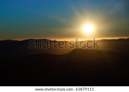 colorful sky and rays from the sun, at sunrise - stock photo