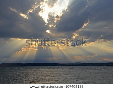 Colorful sky with clouds - Evening sun rays shining through clouds at sea - stock photo