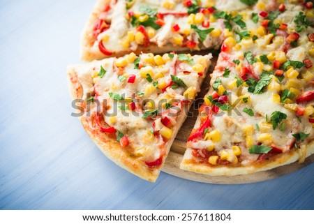 Colorful sliced pizza with mozzarella cheese, chicken, sweet corn, sweet pepper and parsley close up. Italian cuisine. - stock photo