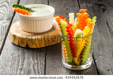 Colorful slices of raw vegetables in glasses (carrots, celery, cucumber, sweet pepper) and yogurt sauce. The concept of diet, healthy and vegetarian food. Selective focus - stock photo