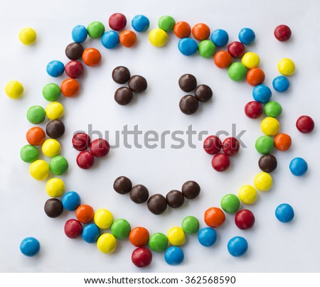 colorful smiley, kind, happy emotional candy face  with blushes on white background made of round candies for children games looks like Kapitoshka