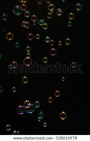 Colorful soap bubbles over black background