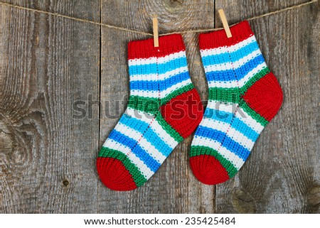Colorful socks hanging on the clothesline on old wooden background   - stock photo