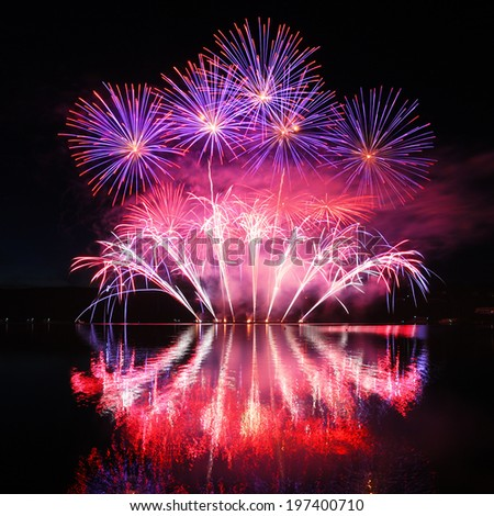 Colorful spectacular fireworks with reflections in the water - stock photo