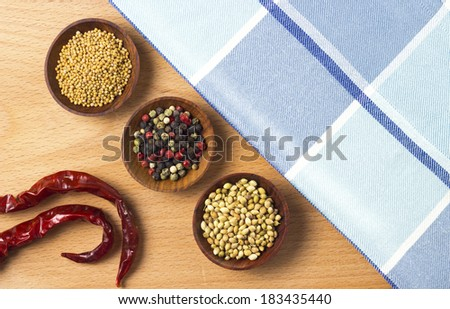 colorful spices and chili peppers on wooden table - stock photo
