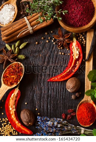 Colorful spices and herbs frame on a wooden background. - stock photo
