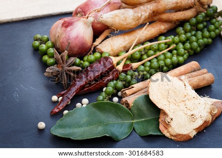 Colorful spices and herbs on a black wooden background.Herb food.