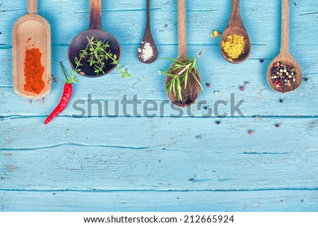 Colorful Spices and herbs on rustic spoons over blue wooden background  - stock photo