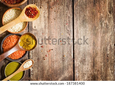 Colorful spices in wooden spoons and spices in a bowls on rustic wooden background