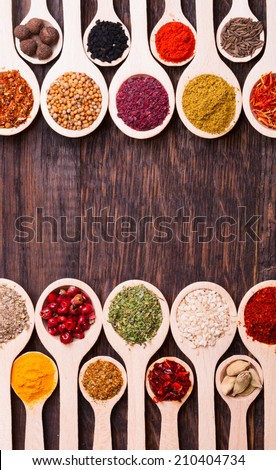 Colorful spices in wooden spoons on wooden background