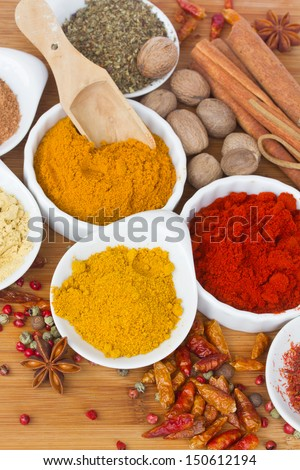 colorful spices of curry, cucrma and red pepper with seeds of anise and nutmeg on wooden table