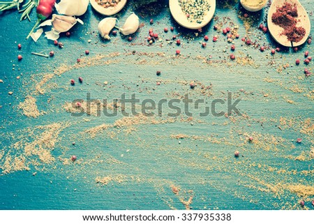 Colorful spices on a black board/toned photo - stock photo