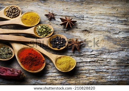 Colorful spices on rustic wooden table - stock photo
