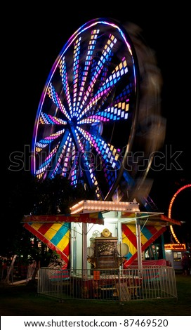 Colorful Spinning Ferris Wheel and Antique Fairground Organ - ferris wheel spins with antique fairground organ in foreground - stock photo