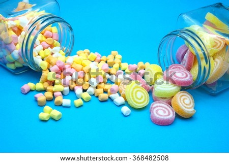 Colorful spiral jelly and colorful marshmallows with glass jars on blue background. Focus on jelly and marshmallows on floor. Space for texts. - stock photo