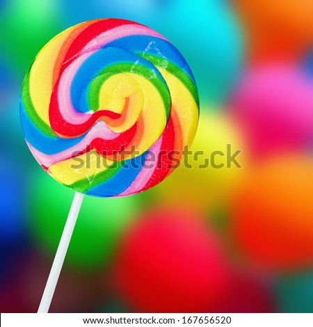 Colorful spiral lollipop on a colored background - stock photo