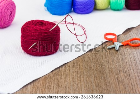 Colorful spools of thread with a needle and scissors