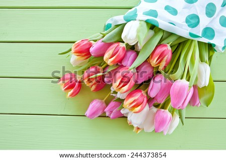 Colorful spring flowers on green wooden boards - stock photo