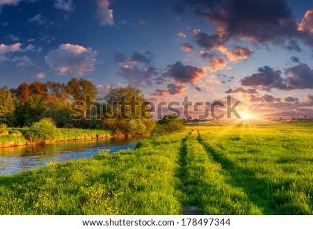 Colorful spring landscape on the river. Dramatic sunset. - stock photo