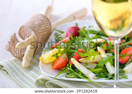 Colorful spring salad with fresh white asparagus, rocket salad and strawberries, served with a glass of dry and fruity white wine  - stock photo