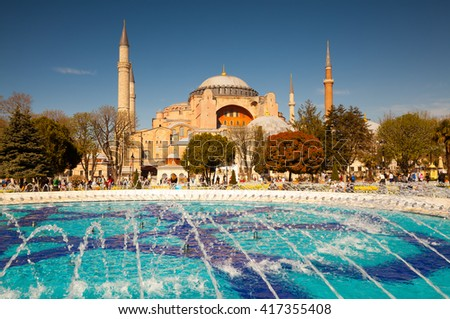 Colorful spring scene in Sultan Ahmet park in Istanbul, Turkey, Europe. Fountain on the background of the Ayasofya Museum (Hagia Sophia). Retro filtered. - stock photo