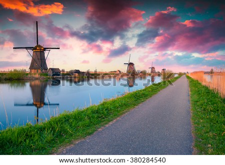 Colorful spring scene in the famous Kinderdijk canals with windmills, UNESCO world heritage site. Sunrise in Dutch village Kinderdijk, walking path in the park, Netherlands, Europe. - stock photo