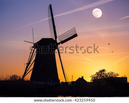 Colorful spring scene in the famous Kinderdijk canals with windmills, UNESCO world heritage site. Sunset with moon in Dutch village Kinderdijk, Netherlands, Europe.