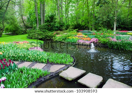 Colorful spring summer park with romantic bridge tulip flowers in a sunny day