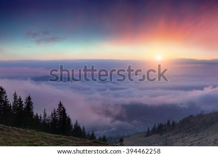 Colorful spring sunrise in the misty mountains. Morning in Carpathian village under sea of fog at April. - stock photo