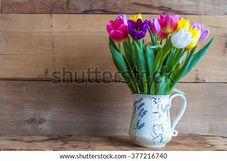 colorful spring tulips in vase and wooden background, free space for text