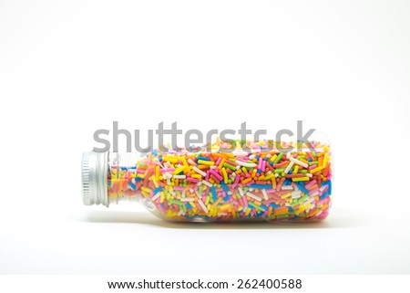 Colorful Sprinkles for Dessert Decorating in Glass Bottle on white background - stock photo