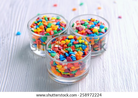 Colorful sprinkles in bowls on table close-up