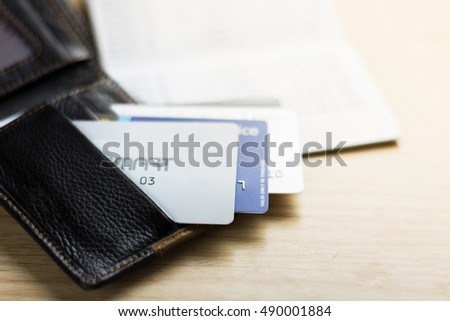 Colorful stack of credit cards and shopping gift cards with wallet on wooden table background. Extremely shallow dof.