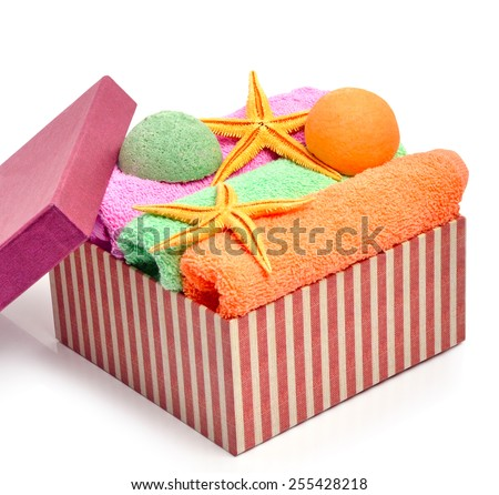 Colorful stacked spa towels, bath bombs and starfishes in the gift box isolated on white - stock photo