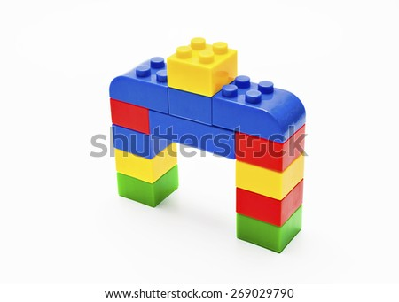Colorful stacked toy building blocks with shape of house. - stock photo