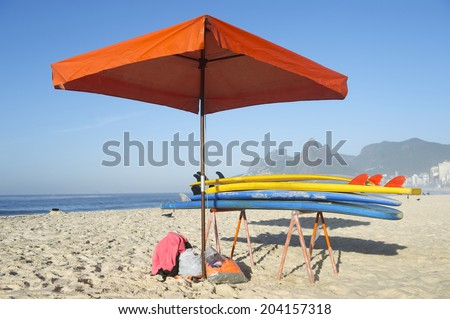 Colorful stand up paddle long board surfboards stacked next to beach umbrella on Ipanema Beach Rio de Janeiro - stock photo